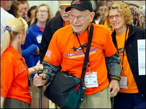 Veteran Paul Meyer, center, is guided through the gate by Beth Emery, Honor Flight of Northwest Ohio Organizer, left, while boarding. Guardian Angela King, right, follows behind.