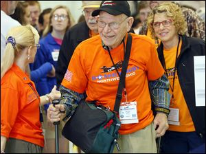 Veteran Paul Meyer is guided through the gate Wednesday by Beth Emery, Honor Flight of Northwest Ohio organizer, left, while boarding the Honor Flight at the Grand Aire hangar at Toledo Express Airport. Following behind him at right is Mr. Meyer's guardian, Angela King.