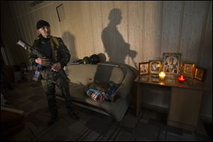 A pro-Russian gunman in camouflage uniform stands guard next to Orthodox icons today inside the Regional Prosecutor's Office building they seized on Tuesday in Luhansk, one of the largest cities in eastern, Ukraine.