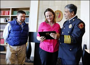 Toledo Fire Chief Luis Santiago, right, presents a plaque honoring deceased Toledo firefighter Stephen Machcinski to his sister, Beth Hoye, with her husband, Chris Hoye, left, during a University of Toledo Emergency Medicine Wall of Honor dedication ceremony at the Radisson Hotel on the UT Health Science Campus.   Plaques for Mr. Machcinski and fellow firefighter James 'Jamie' Dickman, who were killed while fighting a fire earlier this year, were dedicated Wednesday.
