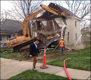 Bill Pulte Jr. walks in front of a Pontiac house being demolished by Pulte's nonprofit Detroit Blight Authority.