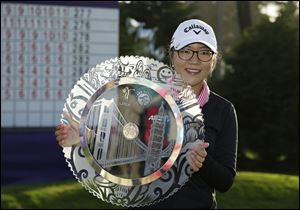Lydia Ko of New Zealand poses with her trophy on the 18th green of the Lake Merced Golf Club after winning the Swinging Skirts LPGA Classic golf tournament earlier in April.