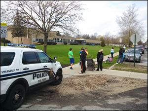 Parents and children wait outside McGregor Elementary School while Toledo  police investigate a 'suspicious package.'
