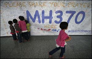 Children read messages and well wishes displayed for all involved with the missing Malaysia Airlines jetliner MH370 on the walls of the Kuala Lumpur International Airport in March.