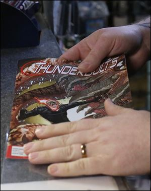Emmerich slides his newly purchased comic book into a protective plastic sleeve.