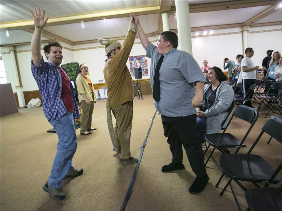 Thomas Stone gets high-fives from Henry, played by Ben Simpson, left, and  Mudge, played by Rob Grippa, after a performance.