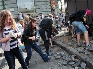 Ukrainian government supporters dig for stones during a clash Friday with pro-Russians in the Black Sea port of Odessa. The city had remained largely untroubled by unrest since the February toppling of President Viktor Yanukovych.