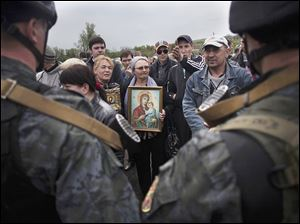 A pro-Russia demonstrator holds an Orthodox painting in front of Ukrainian Army soldiers while blocking the road Friday in Andreevka, Ukraine.  Russia has massed tens of thousands of troops in areas near the border.