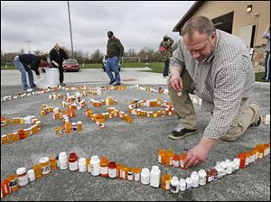 ABOVE: Kyle Schalow of Holland, right, and others build the RX Epidemic Memorial out of empty prescription drug bottles in Homecoming Park in Springfield Township. Mr. Schalow started the  RX Epidemic Memorial Foundation after his wife, April, at left in background, became addicted to prescription pain killers.