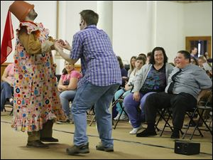 Mudge, played by Rob Grippa, left, and Henry, played by Ben Simpson, act out a scene as Tommy Stone and his mother, Ginnene, at right, laugh during a performance by Theatreworks USA, a nonprofit theater group from New York City, at the Autism Academy of Learning on Friday.