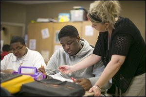 Teacher Tracey Johnson helps eighth-grader Demarko Craig prepare for an upcoming test at Chase STEM Academy. The school expelled Demarko last year for discipline problems. This year is different.