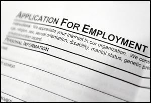 Aan employment application form sits on a table during a job fair at Columbia-Greene Community College in Hudson, N.Y.