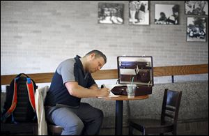 Josh Howarth, University of Toledo senior, studies in the coffee shop in the student union. Economists at the Federal Reserve Bank of New York say that unemployment and underemployment of recent graduates are higher than historical norms.