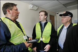 Toledo Land Bank volunteers Paul J. Gibbs, left, and Don Wiebold, right, both of East Toledo discuss the Toledo Survey with David Mann, center, of Toledo.