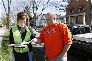 Amy Tingley of Oregon speaks to Jason Ribby, East Toledo homeowner. Ms. Tingley is one of the first volunteers assisting with the Toledo Survey.