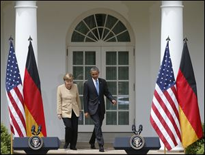 President Barack Obama and German Chancellor Angela Merkel arrive for their joint news conference in the Rose Garden of the White House in Washington.
