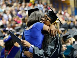 Joslin Smith, 15, a student at Whitmer High School, congratulates her sister, Cortney Carney, right, also of Toledo, as she receives her Bachelor of Social Work.