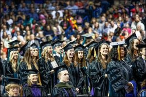 Doctoral candidates rise during spring commencement exercises at the University of Toledo. This month, UT graduated 124 with doctoral, 1,941 with bachelor's, and 554 with master's degrees.