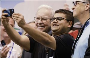 An unidentified shareholder takes a selfie with Berkshire Hathaway Chairman and CEO Warren Buffett, left, and Berkshire board member Bill Gates, right.