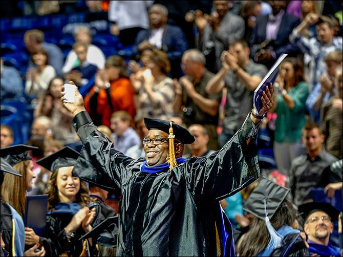 4n1mongomery-5 Richard Montgomery II stands and smiles widely after receiving his doctorate in educational administration.