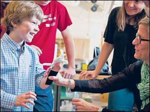 Eight-year-old Steele Songle smiles at his mother, Ellen, after trying on an artificial hand designed by high school engineering students.