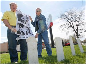 Terry Lodge of Holland, left, and Steve Miller of Toledo, hold a poster with photographs of the four Kent State undergraduates who were killed by Ohio Nationa