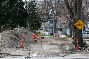 Installation of new sanitary sewer and water lines has left Hillside Drive in Rossford torn up. The city's design consultant has given a city council committee  three plans to repair the street.