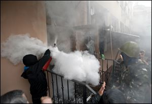 A pro-Russian protester fires a fire extinguisher at riot police inside at a police station building today in Odessa, Ukraine.