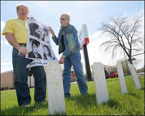 Terry Lodge of Holland, left, and Steve Miller of Toledo, hold a poster with photographs of the four Kent State undergraduates who were killed by Ohio National Guardsmen on May 4, 1970.     Friends of the Northwest Ohio Peace Coalition gathered Sunday on the 44th anniversary of the shootings.