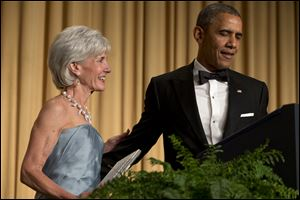 President Barack Obama, right, has outgoing Health and Human Services Secretary Kathleen Sebelius come on stage as part of a joke to fix a technical glitch at the end of his speech.