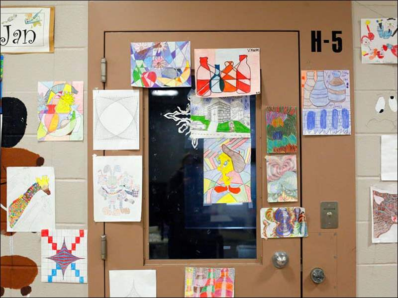 A door and surrounding walls on H Block in the Lucas County Juvenile Detention Center is covered in student inmates' art.