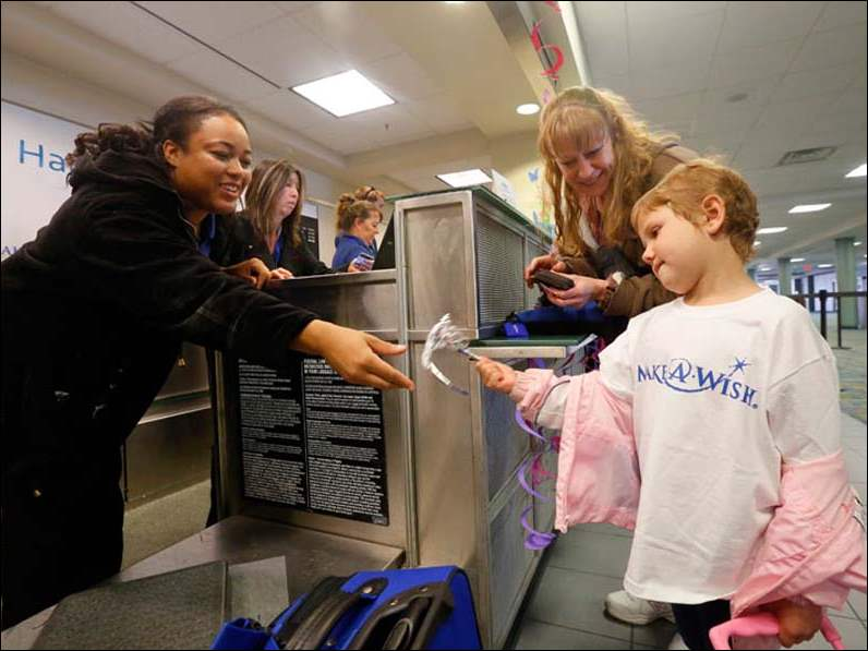 Sharisse Garbutt, left, with Allegiant Air, gives Emily Kwiatkowski, 5, right, a crown while Kwiatkowski's mother Elizabeth Magill, center, stands nearby at the check-in counter at Toledo Express Airport for a princess-themed send-off celebration on her way to Orlando for a Make-A-Wish trip Sunday.