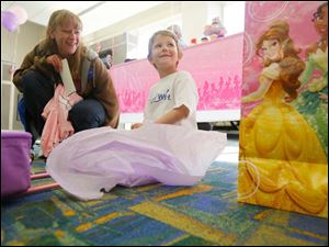 Emily Kwiatkowski, 5, right, and her mother Elizabeth Magill, left, open presents near the airport gate.