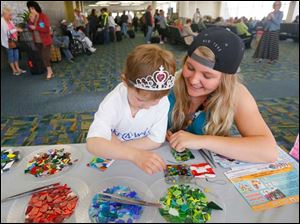 Emily Kwiatkowski, 5, left, and her cousin Chelsea Heil, right, make a glass ornament at a Copper Moon Studio Gallery & Gifts table near the Allegiant gate during a princess-themed send-off celebration on her way to Orlando for a Make-A-Wish trip.