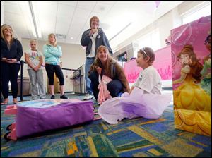 Emily Kwiatkowski, 5, right, and her mother Elizabeth Magill, left, open presents near the gate for a princess-themed send-off celebration on her way to Orlando.