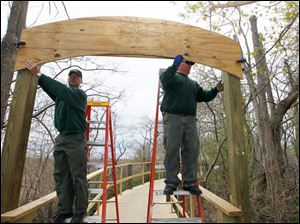 ODNR employees Patrick Baranowski, area manager, left, and Andy Thompson, as they prepare a new sign on the boardwalk for a dedication ceremony to be held Saturday, May10th.