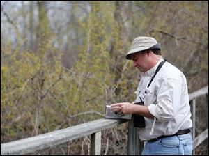 Andy Tata, of Monroe, Mich., verifies the identity of a bird in his book.