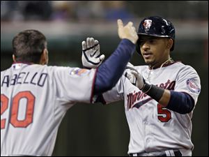 Minnesota Twins' Eduardo Escobar (5) celebrates his solo home run off Cleveland Indians relief pitcher John Axford with Chris Colabello (20) in the 10th inning.