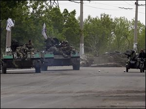 Pro-Russian gunmen atop armored personal carriers passing by barricades on a road leading into Slovyansk, eastern Ukraine, today.