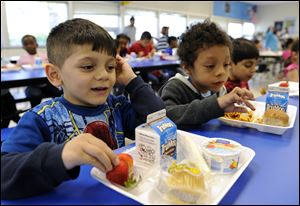 Biden Arias-Romers, 5, left, and Nathaniel Cossio-Boatwright, 6, right, eat lunch at the Patrick Henry Elementary School in Alexandria, Va.