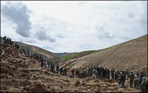 Survivors walk and search for their relatives' bodies today at the site of Friday's landslide.