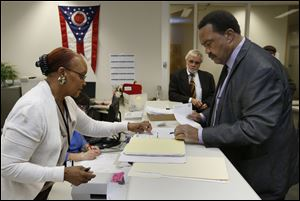 Election worker June Boyd helps Jack Ford file his petitions today at the Lucas County Board of Elections in Toledo. The independent candidate is running for State Senate District 11.