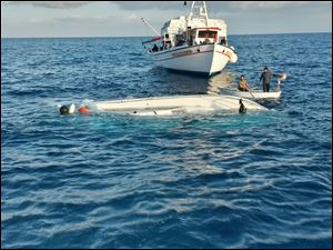 Local fishermen look a yacht used to transport immigrants illegally that overturned in a fatal accident near the Greek island of Samos today.