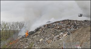 A file photo of Toledo firefighters working on a fire at a Stickney Recycling debris pile in Toledo.