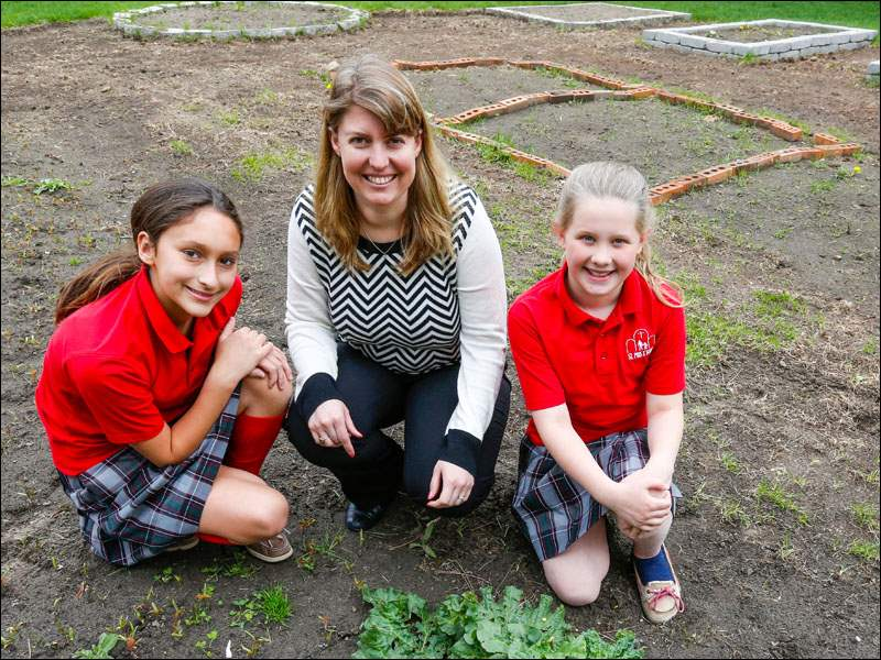 From left: 5th grader Maria Richard, 5th grade teacher Jen Ohms and 5th grader Lauren Hitts pose by a rhubarb plant that's growing in their St. Pius X School garden in Toledo.