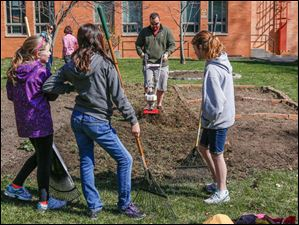 5th graders Lauren Hitts, from left, and Maria Richard, and 6th grader Emma Bodmer wait for Fred Bodmer to remove grass from around the garden beds.