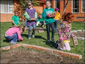 Daisy girl scouts Isabella Polston, from 3rd from right, Callan Horoszewski and Elena Rodriquez carry bricks to border a garden bed.