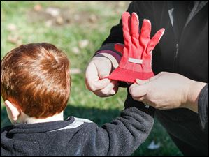 Ryan Brehmer, 3, gets help putting on gloves by his mom, Daisy girl scout leader Elizabeth Brehmer.
