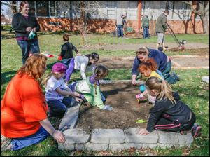 Volunteers, parents and students plant seeds during