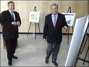 U.S. Census Bureau Director John Thompson, left, looks on as North Dakota Gov. Jack Dalrymple shows him one of the charts illustrating large growth in North Dakota counties during a news conference.